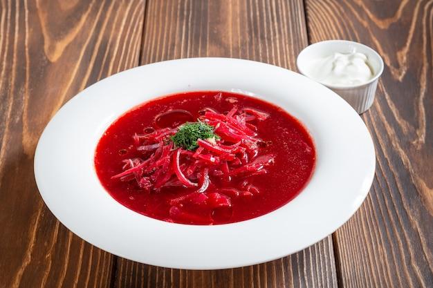 Assiette de soupe bortsch russe traditionnelle sur table en bois