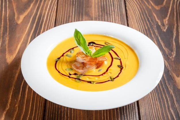 Assiette de soupe à la citrouille aux crevettes et basilic sur table en bois