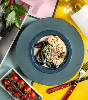 Une assiette de soupe crémeuse aux fruits de mer avec des crevettes et des moules
