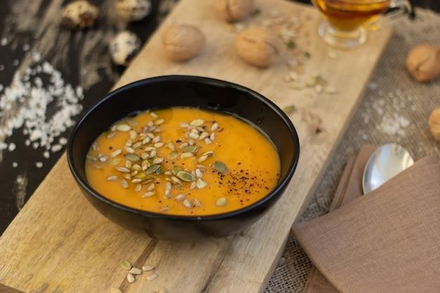 Assiette de soupe de potiron sur planche à découper en bois