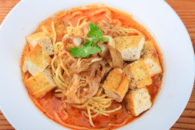 Assiette de soupe avec des spaghettis, des morceaux de pain et décorée de légumes verts