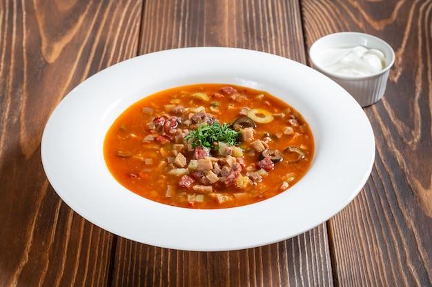 Assiette soupe à la viande russe traditionnelle solyanka sur table en bois