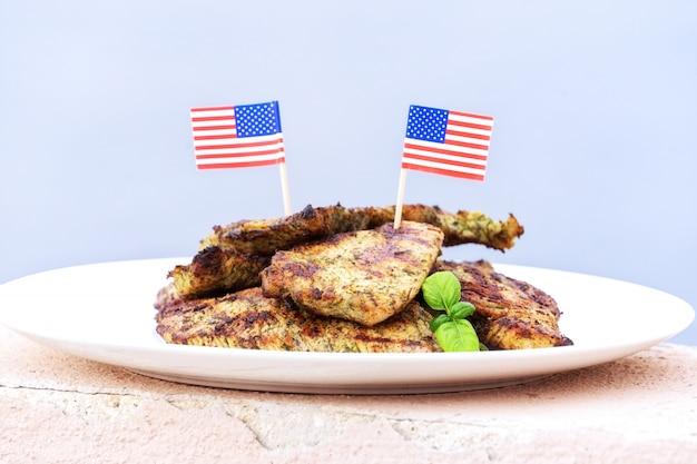 Assiette avec des steaks de dinde cuits sur le gril avec des drapeaux américains