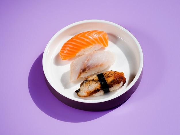 Assiette de sushi blanche sur fond bleu