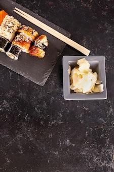 Assiette de sushi sur pierre sombre à côté de gingembre sur fond noir avec fond disponible