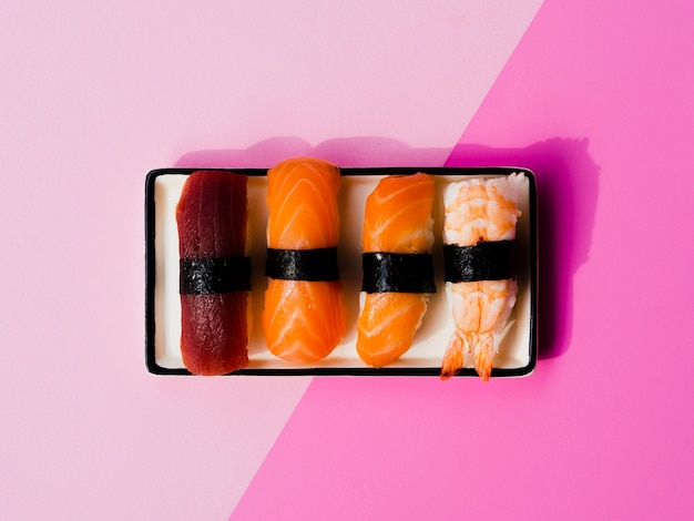 Assiette de sushis variaton sur fond rose
