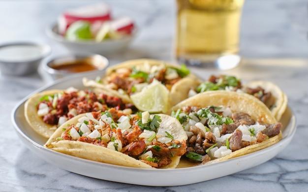 Assiette de tacos de rue mexicains avec carne asada, chorizo et al pastor dans des tortillas de maïs