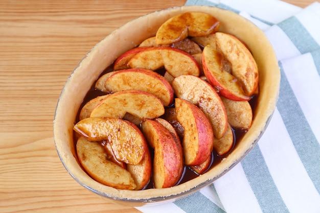 Assiette à tarte avec garniture mixte fraîche avant de cuire une tarte aux pommes maison