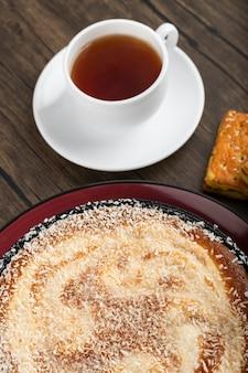 Assiette de tarte sucrée avec pépites de noix de coco, tasse de thé et biscuits sur une surface en bois