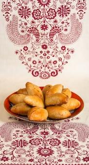 Assiette avec des tartes rouges fraîchement cuites sur le fond d'une nappe avec un motif