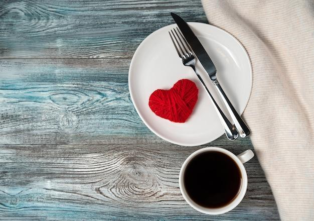 Assiette, tasse de café, un coeur et un pull sur un fond en bois avec espace pour copier.