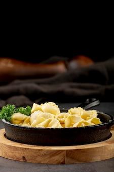 Assiette de tortellini sur un support en bois