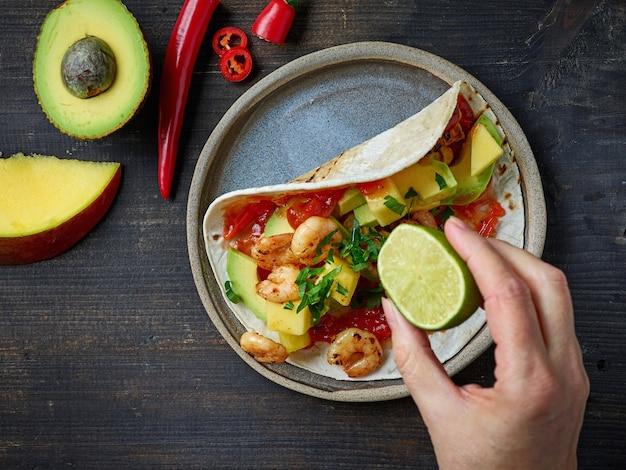 Assiette de tortilla et légumes sur la vue de dessus de table en bois noir