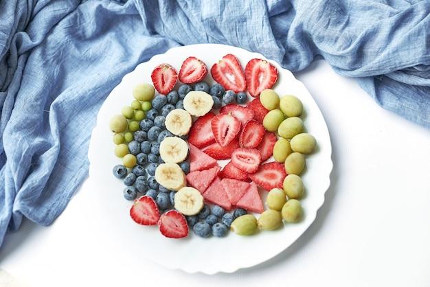 Assiette avec des tranches de fruits surgelés végétariens: arbuk, myrtilles, myrtilles, banane avec yaourt