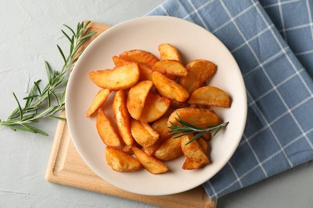 Assiette avec des tranches de quartiers de pommes de terre au four, serviette sur fond gris. vue de dessus, gros plan