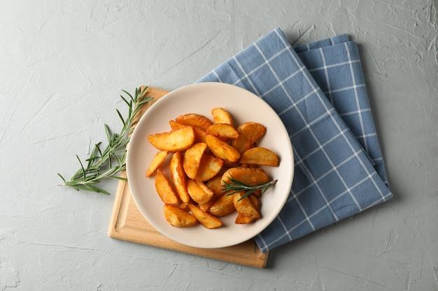 Assiette avec des tranches de quartiers de pommes de terre au four, serviette sur fond gris. vue de dessus