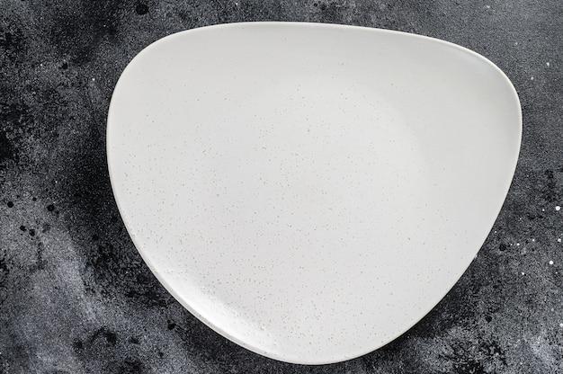 Assiette triangulaire vide blanche, fond de restaurant. vue de dessus. espace copie