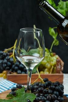 Une assiette de variété de raisins avec un verre de vin blanc sur table blanche avec bouteille de vin