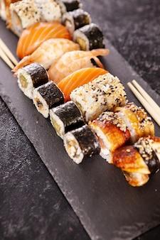 Assiette avec variété de sushis sur fond de pierre sombre. cuisine saine