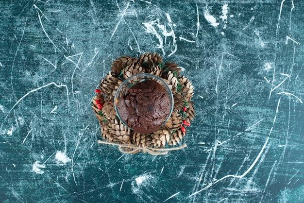 Une assiette en verre avec biscuit au chocolat et couronne de noël. photo de haute qualité