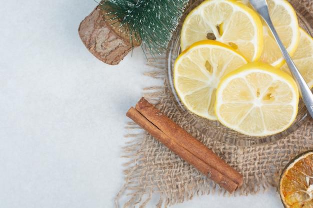 Une assiette en verre de citron avec des bâtons de cannelle sur un sac. photo de haute qualité