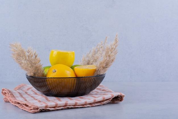 Assiette en verre de citrons juteux frais sur table en pierre.