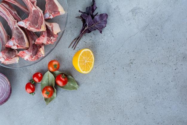 Assiette en verre de côtelettes d'agneau aux légumes bio sur pierre.
