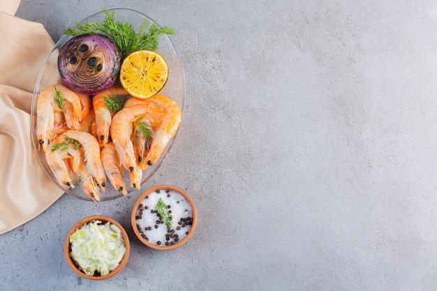Une assiette en verre de délicieuses crevettes avec des tranches de citron et d'oignon sur une surface en pierre