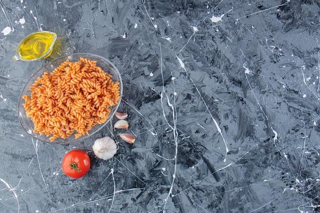 Assiette en verre de délicieuses pâtes fusilli et légumes sur fond de marbre.