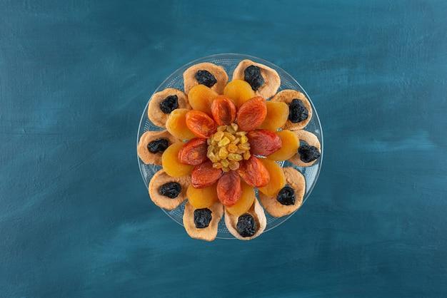 Assiette en verre de divers fruits secs placés sur table bleue.