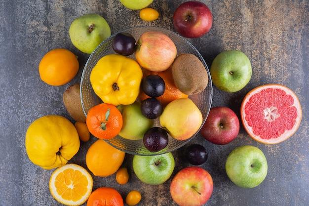 Assiette en verre de fruits frais au-dessus de nombreux fruits.