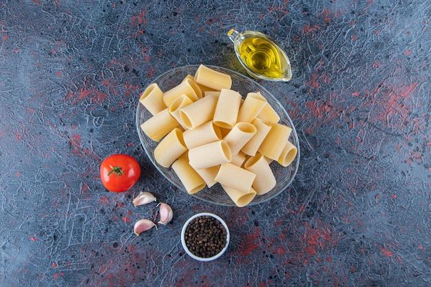 Une assiette en verre de pâtes cannelloni crues à l'ail et à l'huile sur une surface sombre.