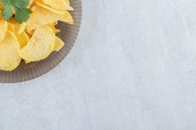 Assiette en verre de savoureux chips d'ondulation sur pierre.
