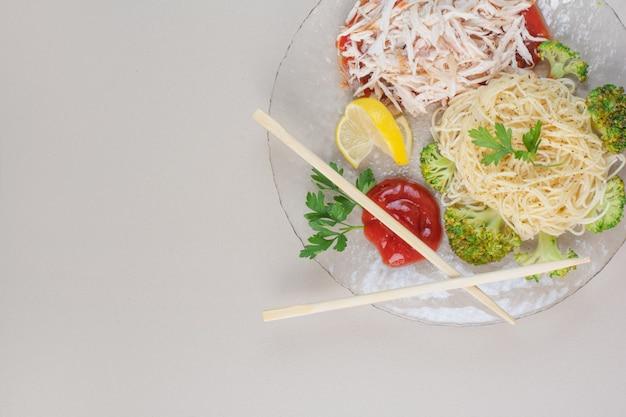 Assiette en verre de spaghetti, poulet et légumes sur une surface blanche