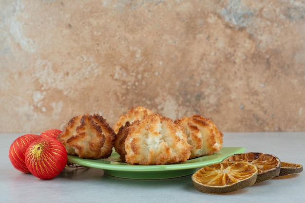 Une assiette verte de biscuits sucrés ronds avec des oranges séchées et des boules de noël.