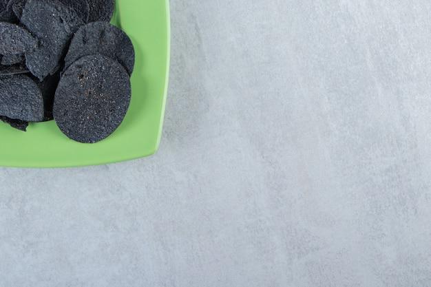 Assiette verte de chips noires croustillantes salées sur pierre.