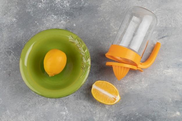 Une assiette verte de citron entier avec une tranche et un pichet en verre vide sur du marbre.