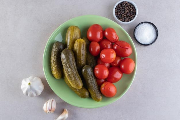 Assiette verte de concombres et tomates marinés sur table en pierre.