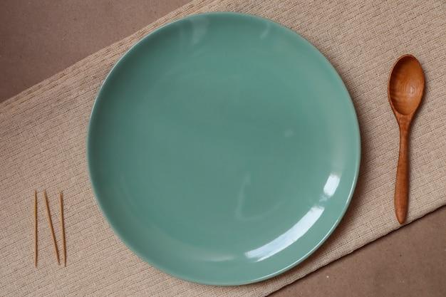 Assiette verte et cuillère en bois sur une nappe crème prête à manger