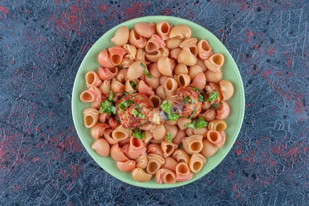 Une assiette verte avec des cuisses de poulet frites avec des macaronis.