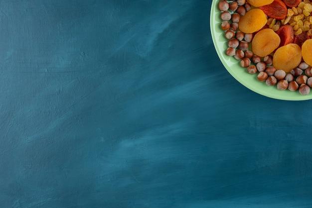 Assiette verte de fruits secs et de noisettes sur table bleue.