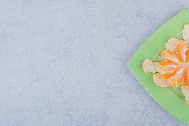 Une assiette verte de mandarine aigre tranchée sur fond blanc. photo de haute qualité