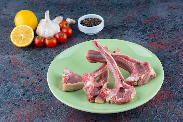 Assiette verte de membres d'agneau non cuits avec des légumes sur du marbre.