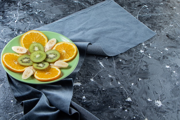 Assiette verte d'orange, de kiwi et de banane en tranches sur une surface en marbre.