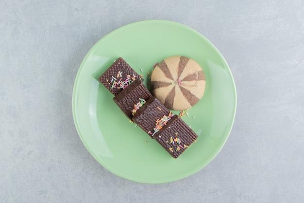 Une assiette verte pleine de gaufres au chocolat.