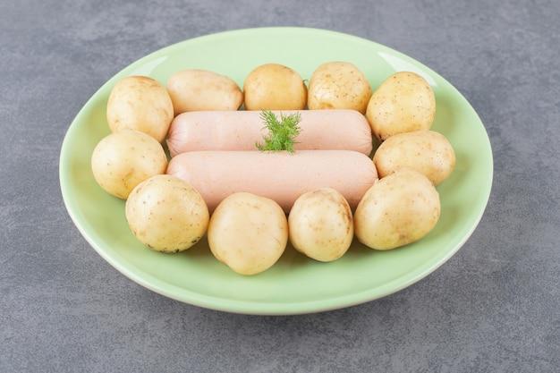 Une assiette verte avec des saucisses bouillies et des pommes de terre bouillies.
