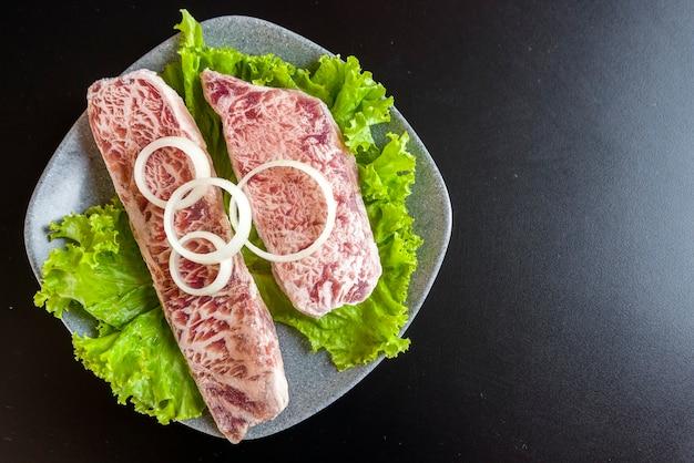 Assiette avec de la viande crue pour griller sur une table noire
