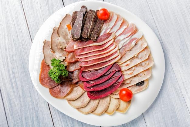 Assiette de viande avec de délicieux morceaux de jambon en tranches, tomates cerises, herbes et viande