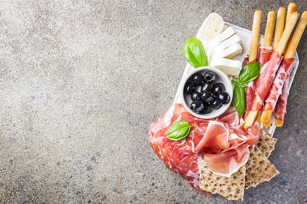 Assiette de viande froide avec du fromage, des olives et du pain sur une planche à découper sur une surface en pierre grise