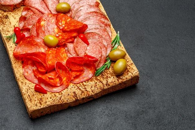 Assiette de viande froide avec saucisson salami et chorizo sur planche de bois de liège